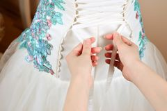 Bruden hjälps att snöra åt upp korsetten fotografering för bildbyråer