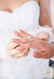 Bruden i den vita klänningen som sätter vigselringen på brudgummar, fingrar Royaltyfria Foton