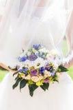 Bruden i den vita satängklänningen med skyler och bröllopbukett Arkivfoto