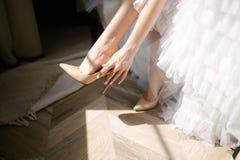 Bruden i en bröllopsklänning sätter skor på hennes fot arkivfoton