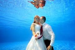 Bruden i en bröllopsklänning som kramar en brudgum som är undervattens- i pölinnehavblommor i henne hand och ser kameran Arkivfoto