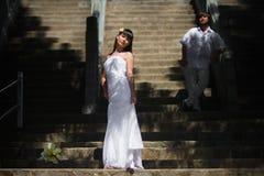 Bruden i en elegant bröllopsklänning står på bakgrunden av en stor trappuppgång och bak henne är brudgummen i vit kläder arkivbilder