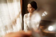 Bruden i härligt klänningsammanträde på stol inomhus i den vita studioinre gillar hemma Moderiktigt bröllopstilskott royaltyfri fotografi