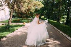 Bruden kör playfully längs gränden av stenar Flickan i bröllopsklänningen har roligt och rinnande bort royaltyfri bild