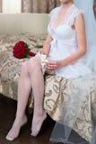Bruden klär strumpebandet på benet Bild av den härliga kvinnliga stången Royaltyfri Bild