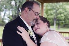 Bruden lägger huvudet på brudgumskuldra Royaltyfri Fotografi