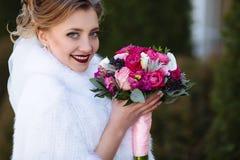 Bruden med blont hår och fransk manikyr ler och visar hennes härliga bukett Nära sikt av framsidan för brud` s royaltyfria bilder
