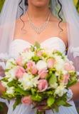 Bruden med ett armband runt om halsinnehav blommar arkivbild