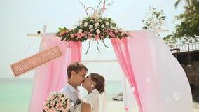 Bruden och brudgummen är kyssande Bröllopceremoni på stranden av Filippinerna lager videofilmer