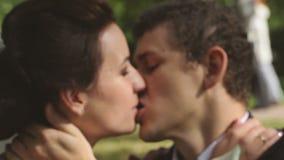 Bruden och brudgummen är kyssande parkerar in stock video