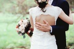 Bruden och brudgummen, arm i arm, under naturlig grönska Händer av nygifta personer tillsammans binder crystal smycken för parcra Arkivfoto