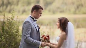 Bruden och brudgummen dansar utomhus i en parkera nära sjön lyckligt tillsammans bröllop för tappning för klädpardag lyckligt stock video