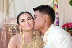 Bruden och brudgummen delar en kyss Arkivfoto