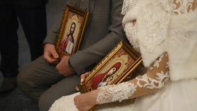 Bruden och brudgummen får gifta i kyrka De lyssnar till hållande symboler för prästmannen i deras händer stock video