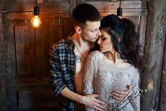 Bruden och brudgummen får klara i morgonen för bröllopet Älska par som hemma kramar Stilig brudgum och charmig brud Arkivfoto