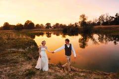 Bruden och brudgummen går i aftonen mot bakgrunden av sjön i den röda solnedgången generalplan Royaltyfri Foto