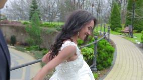 Bruden och brudgummen går i parkera stock video