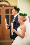 Bruden och brudgummen ger ett löfte av förälskelse i kyrkan  Arkivbild
