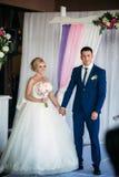 Bruden och brudgummen ger ett löfte av förälskelse i kyrkan  Royaltyfri Foto