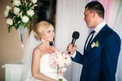 Bruden och brudgummen ger ett löfte av förälskelse i kyrkan  Arkivfoto