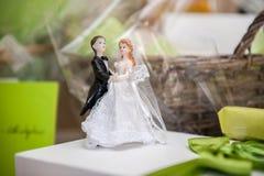 Bruden och brudgummen gjorde av socker överst av bröllopstårtan arkivfoton