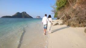 bruden och brudgummen går barfota längs kanten av vatten vid klippor lager videofilmer