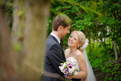 Bruden och brudgummen går i den lyckliga parkera Royaltyfri Foto