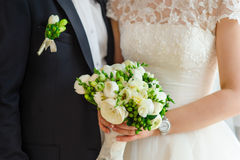 Bruden och brudgummen håller den brud- buketten Arkivfoto