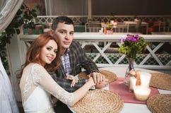 Bruden och brudgummen har den romantiska matställen i gatakafé arkivbilder