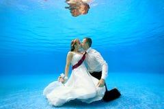 Bruden och brudgummen i bröllopsklänningar omfamnar och kysser undervattens- längst ner av en simbassäng Arkivbilder
