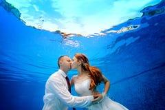 Bruden och brudgummen i bröllopsklänningar omfamnar och kysser undervattens- i pölen på en blå bakgrund Royaltyfri Foto