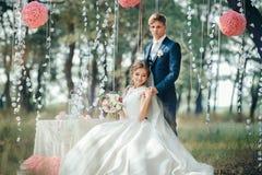 Bruden och brudgummen i bröllopsklänningar på naturlig bakgrund Oss royaltyfri foto