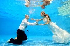 Bruden och brudgummen i bröllopsklänningar simmar undervattens- i pölen för att möta sig Arkivbilder