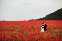 Bruden och brudgummen i ett vallmofält Royaltyfri Foto