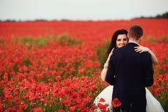 Bruden och brudgummen i ett vallmofält Royaltyfria Foton