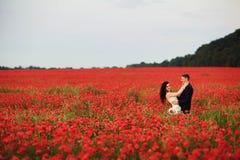 Bruden och brudgummen i ett vallmofält Royaltyfria Bilder