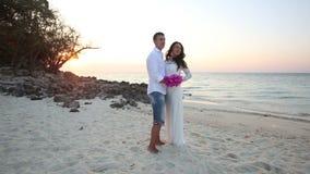 Bruden och brudgummen kramar och skrattar på sandstranden på gryning stock video