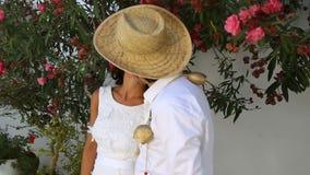 Bruden och brudgummen kysser mot bakgrunden av ett blomningträd Boho stil Grekland lager videofilmer