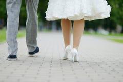 Bruden och brudgummen lägger benen på ryggen Arkivfoton
