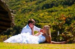 Bruden och brudgummen ligger på gräset arkivbild