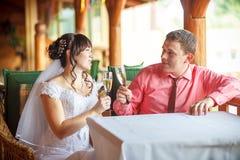Bruden och brudgummen med champagneexponeringsglas Royaltyfri Fotografi