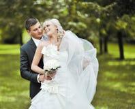 Bruden och brudgummen omfamnar varje annan och skratta på deras bröllop Arkivbild