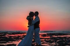 Bruden och brudgummen på solnedgången Royaltyfri Bild
