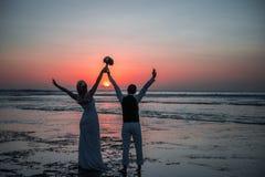 Bruden och brudgummen på solnedgången Arkivfoto