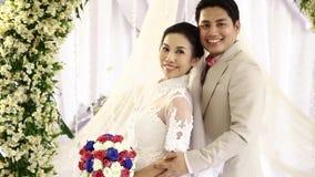 Bruden och brudgummen poserar för att gifta sig bilden arkivfilmer