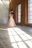 Bruden och brudgummen poserar nära fönster- och tappningtegelstenväggen med sha royaltyfria bilder