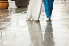 Bruden och brudgummen promenerar den våta trottoargatan fotografering för bildbyråer
