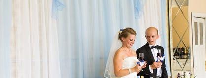 Bruden och brudgummen rymmer champagneexponeringsglas Royaltyfri Bild