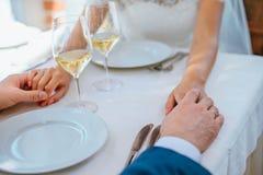 Bruden och brudgummen rymmer varje - annat handen i en restaurang royaltyfria bilder