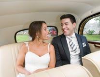 Bruden och brudgummen sitter inom en retro bil och le. Royaltyfria Bilder